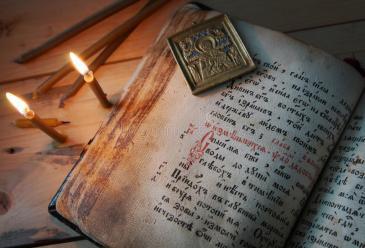 velas-ardientes-y-viejo-icono-del-metal-en-el-libro-antiguo-abierto-52445926